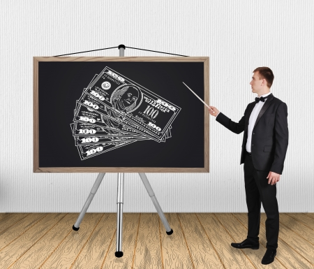 businessman in tuxedo pointing on blackboard with dollars photo