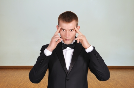 young businessman thinking in room photo