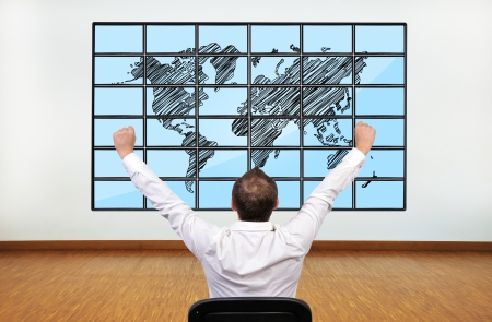 happy businessman looking at map of world on flat panels photo