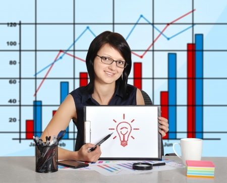 woman with clipboard sitting in office photo
