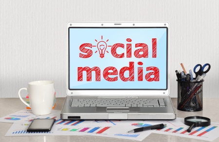laptop on table with social media Фото со стока