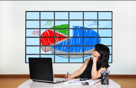 businesswoman in office looking at plasma with chart photo