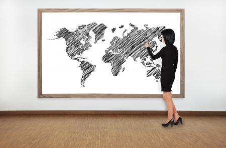 worl: businesswoman drawing worl map on blackboard