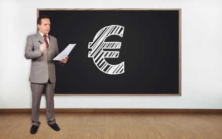 businessman standing in office and drawing euro symbol on  blackboard photo