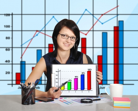 woman sitting in office and chart on clipboard photo