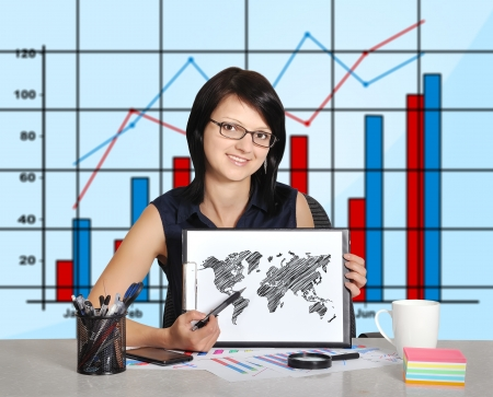woman sitting in office and world map on clipboard photo