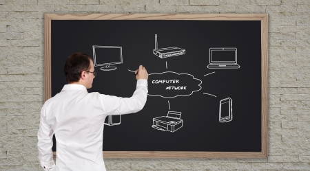 young businessman drawing computer network on blackboard Stock Photo - 22086056
