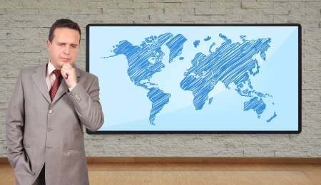 world thinking: businessman thinking and plasma with world map on wall