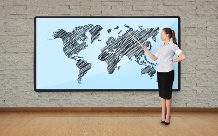 businesswoman in office pointing at  plasma with world map photo