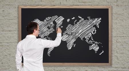 young businessman drawing world map  on blackboard photo
