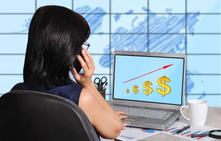 businesswoman and dollar chart on screen laptop sitting in office photo