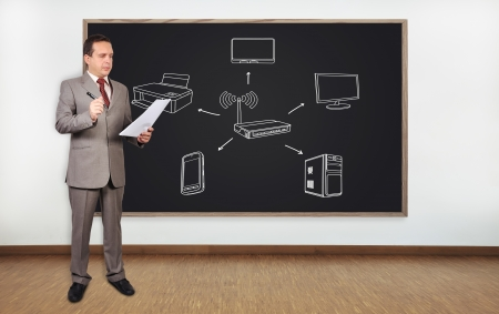 businessman standing in office and blackboard with computer network photo
