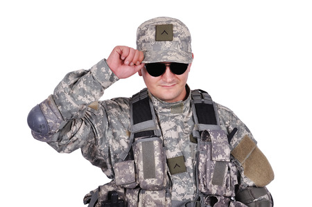 fatigues: US soldier adjusts his cap on white background