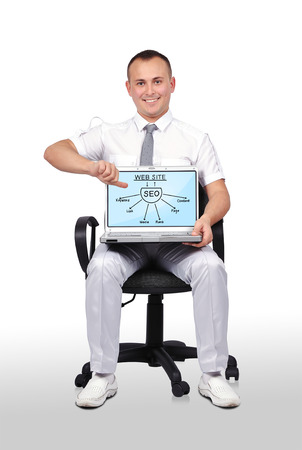 man sitting on chair and holding laptop with seo graph photo