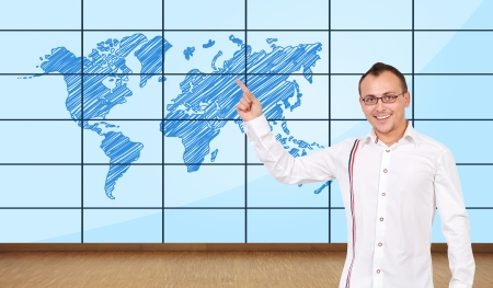 happy man pointing at world map on plasma wall photo