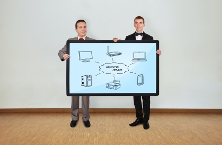 two businessman in room holding plasma panel with computer network photo