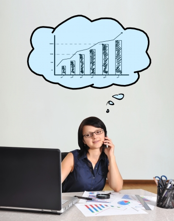businesswoman sitting in office and talking on phone photo