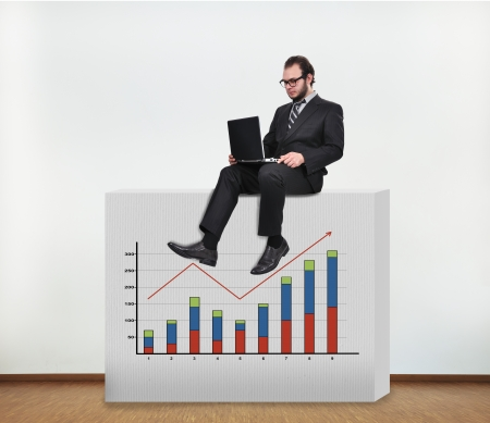 businessman sitting on concrete wall with graphic photo