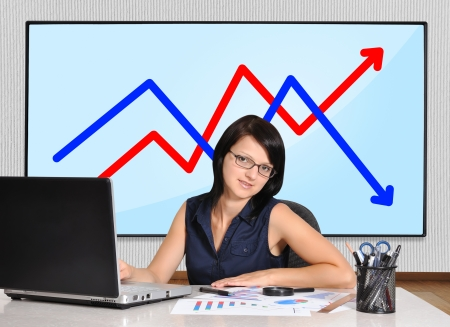woman sitting in office and plasma panel with chart photo