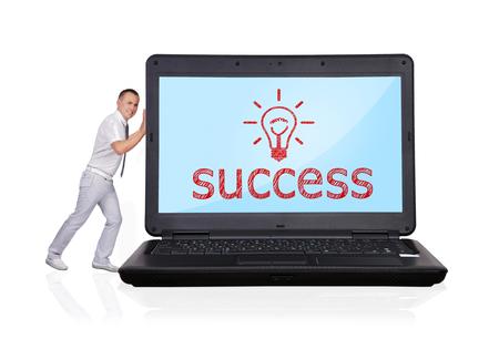 empujando: hombre de negocios empujando portátil grande con el símbolo de éxito Foto de archivo