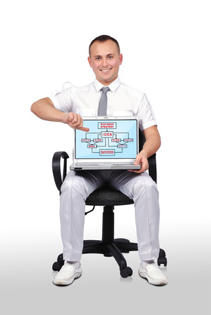 businessman sitting on chair and holding laptop with business scheme photo