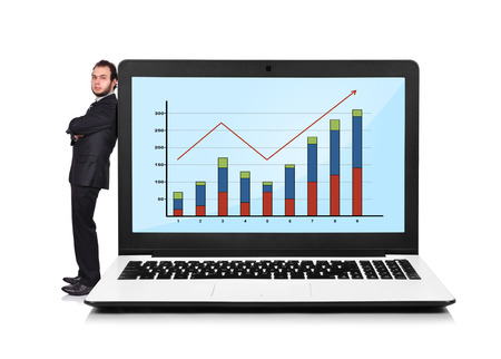Businessman leaning on a laptop with chart photo
