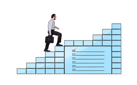 businessman walking up stairs of monitors with checklist photo