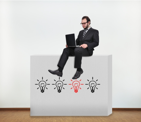 businessman sitting on concrete wall with idea concept photo