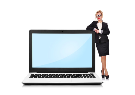 businesswoman standing near a laptop photo