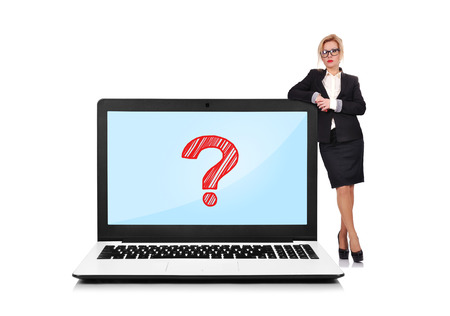 businesswoman standing near a laptop with question mark photo