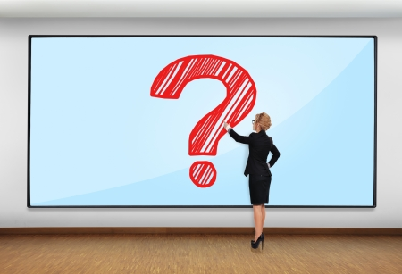 businesswoman pointing to big plasma with question mark photo