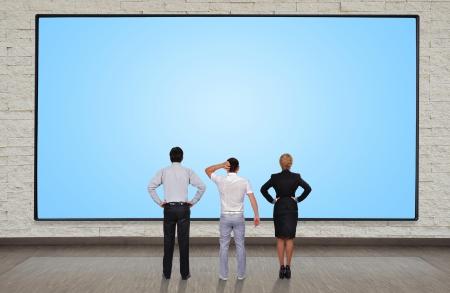 businesspeople looking at blank plasma panel