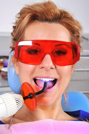 ultraviolet: woman teeth stopping treatment with dental curing ultraviolet light equipment Stock Photo