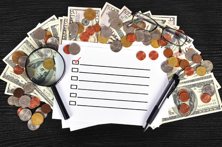 money on table and paper with check box photo