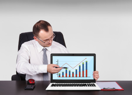 businessman pointing to screen laptop with chart photo