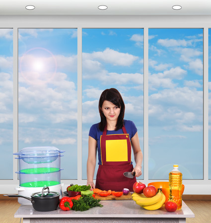 girl chef in kitchen cutting vegetables photo