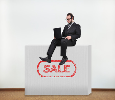 businessman sitting on concrete wall with sale photo