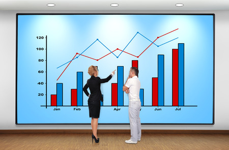 businesswoman and businessman looking at plasma panel with graph photo