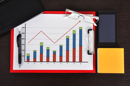 clipboard with graph on table and business object photo