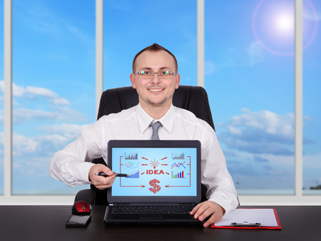 happy businessman pointing to screen laptop with business plan photo