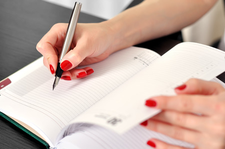 hand with fountain pen writing or signing on a blank diary photo