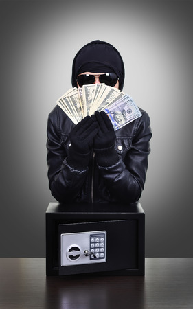 Thief holding a stolen dollars on black background photo