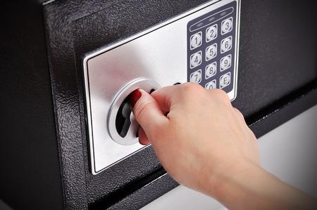 caja fuerte: mano de la mujer abrió una caja fuerte, de cerca