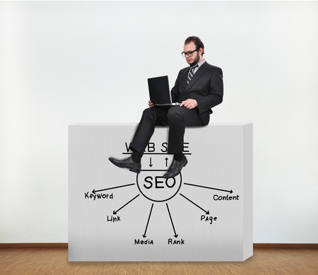 businessman sitting on concrete wall with drawing seo scheme photo