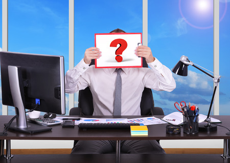 young businessman holding clipboard with question mark photo