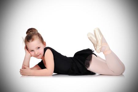 little girl ballerina lies on white floor