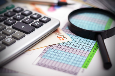 financial table with calculator and magnifying glass photo