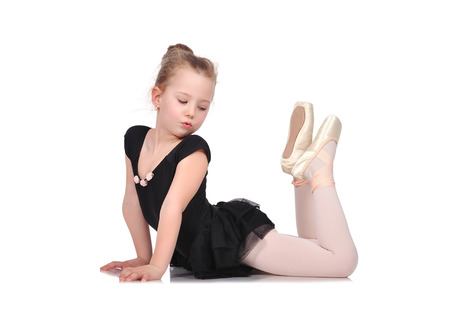 little girl ballerina lies on white floor photo