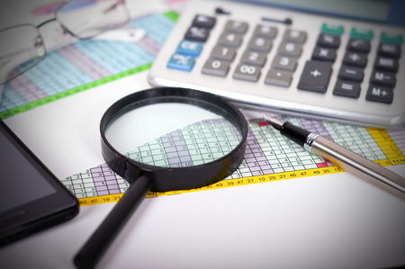 Business concept with magnifying glass, calculator and documents photo