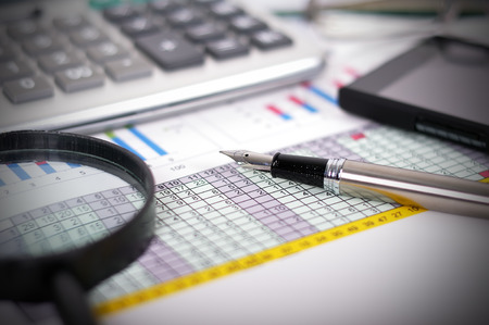Business concept with documents, calculator and magnifying glass photo